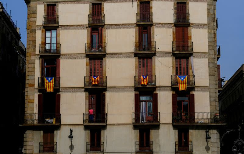 FILE PHOTO: A woman cleans the windows of a house underneath Esteladas (Catalan separatist flags) hanging on balconies at Sant Jaume Square in Barcelona
