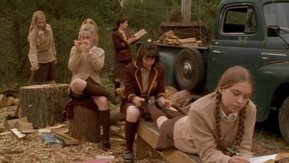 The girls of The Hairy Bird relax together around a wood chopping area