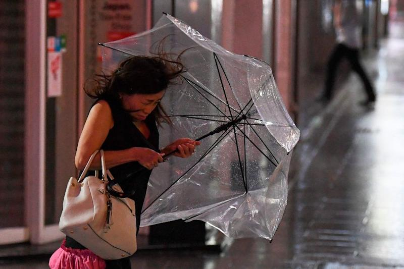 A woman holds her umbrella as wind is grows in Tokyo on Sept. 8, 2019.