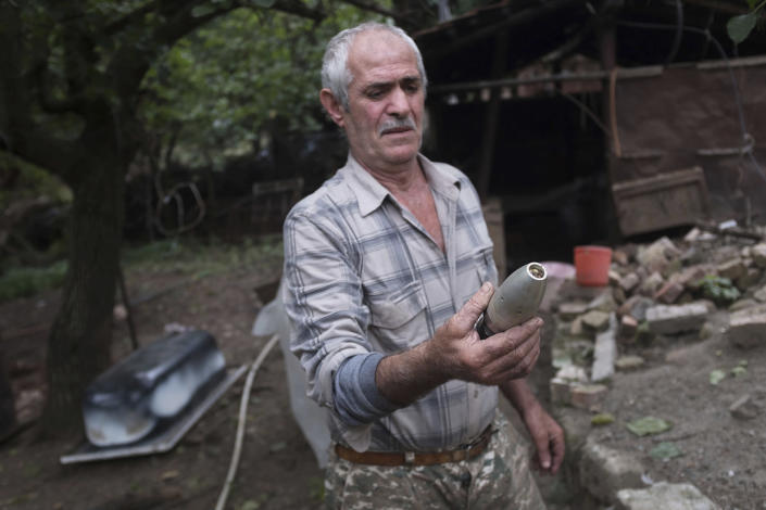 A local resident holds a warhead body that he founded in his yard after an Azerbaijan artillery attack in Hadrut province of self-proclaimed Republic of Nagorno-Karabakh, Azerbaijan, Thursday, Oct. 1, 2020. Two French and two Armenian journalists have been injured in the South Caucasus separatist region of Nagorno-Karabakh, where heavy fighting between Armenian and Azerbaijani forces this week marked the biggest escalation in years of a decades-old conflict. (Karo Sahakyan/ArmGov PAN Photo via AP)