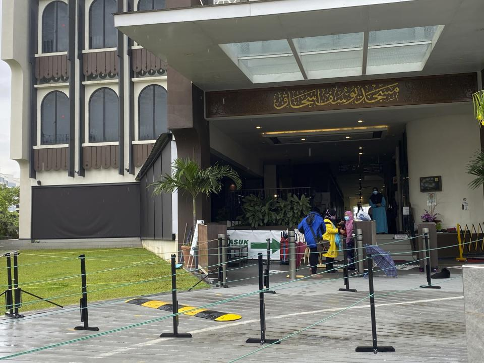 Worshippers enter the Yusof Ishak Mosque in Singapore, Thursday, Jan. 28, 2021. Two Singapore mosques at the center of a foiled terrorist attack by a 16-year-old student stayed open Thursday as police stepped up patrols around the district. (AP Photo/Annabelle Liang)