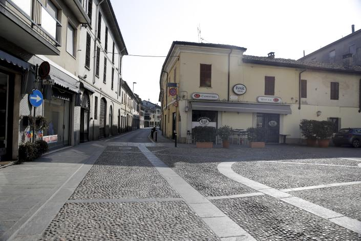 A deserted road in the town of Codogno, near Lodi, Northern Italy, Saturday, Feb. 22, 2020. A dozen northern Italian towns were on effective lockdown Saturday after the new virus linked to China claimed two fatalities in Italy and sickened an increasing number of people who had no direct links to the origin of the virus. The secondary contagions prompted local authorities in towns in Lombardy and Veneto to order schools, businesses and restaurants closed, and to cancel sporting events and Masses. (AP Photo/Luca Bruno)