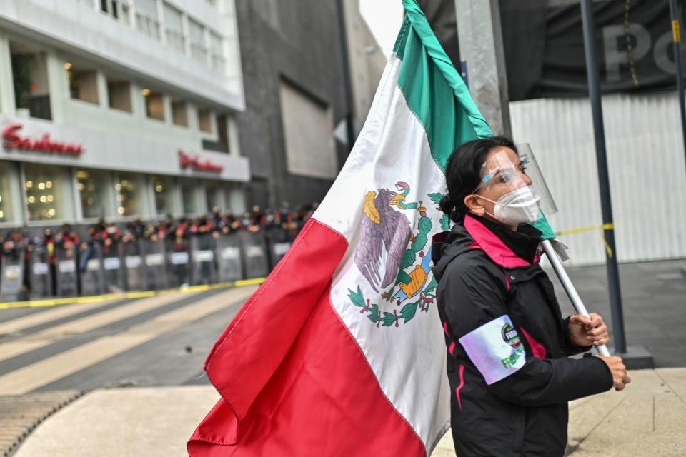 A member of the National Front Anti-AMLO (Frena), who will make a second attempt to reach Zocalo Square to protest against Mexican President Andres Manuel Lopez Obrador (ALMO), holds a Mexican flag as they camp on Juarez street in Mexico City on September 20, 2020, a day after being prevented by the local police to get to the city's main square, amid the COVID-19 novel coronavirus pandemic. (Photo by Pedro PARDO / AFP) (Photo by PEDRO PARDO/AFP via Getty Images)