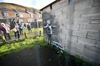 Metal fencing protects an artwork by street artist Banksy, which has appeared on a garage wall in Taibach, Port Talbot, south Wales. The painting appeared overnight and shows a child playing in the falling ash and smoke from a fire in a skip.
