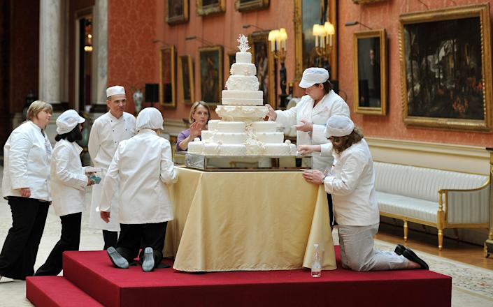 The team led by Fiona Cairns (not in picture) that made the Royal wedding cake, put on the finishing touches for Prince William and Kate Middleton, in the Picture Gallery of Buckingham Palace in central London, today.   (Photo by John Stillwell/PA Images via Getty Images)
