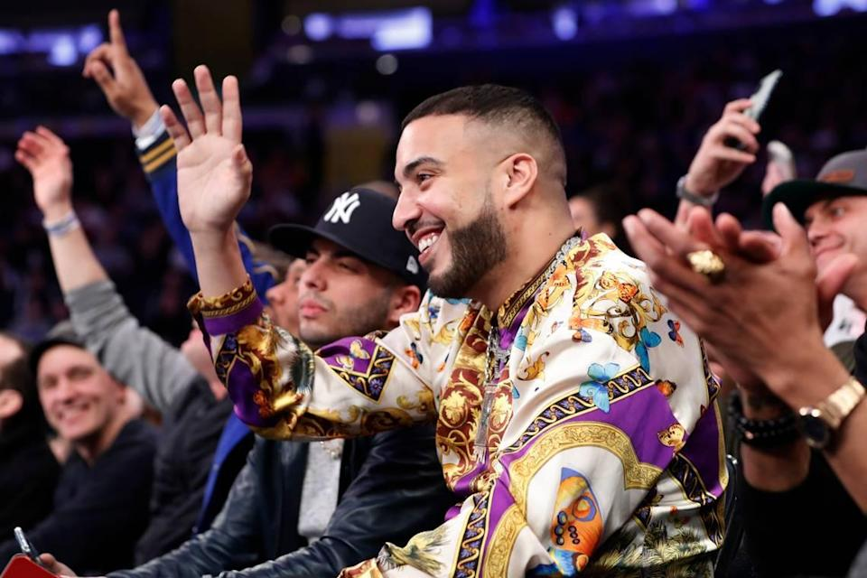Three-time Grammy nominated rapper French Montana waves to the crowd during the first half of an NBA basketball game between the New York Knicks and the Detroit Pistons in New York, Sunday, March 8, 2020. (AP Photo/Kathy Willens)