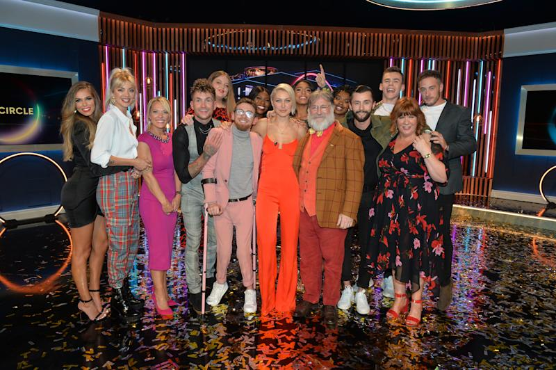 Winner Paddy Smyth (in pink), host Emma Willis (cente) and Viewer's Champion Tim Wilson celebrate with the other finalists and blocked contestants after the final of the second series of Channel 4's The Circle in Salford, Manchester. (Photo by Peter Powell/PA Images via Getty Images)