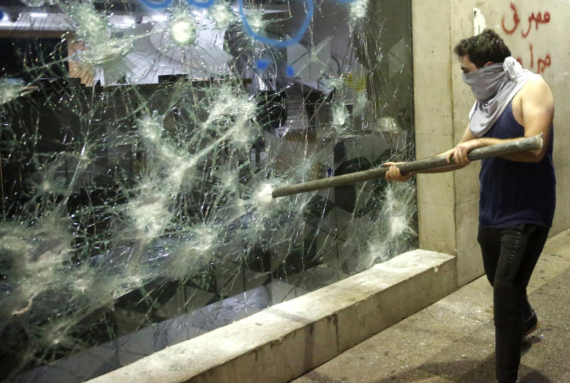An anti-government protester smashes a bank widow, during ongoing protests against the Lebanese central bank's governor and against the deepening financial crisis, at Hamra trade street, in Beirut, Lebanon, Tuesday, Jan. 14, 2020. Lebanese security forces lobbed tear gas at protesters who responded with rocks outside the country's central bank Tuesday, a violent turn after demonstrators returned to the streets following a weekslong lull. (AP Photo/Hussein Malla)