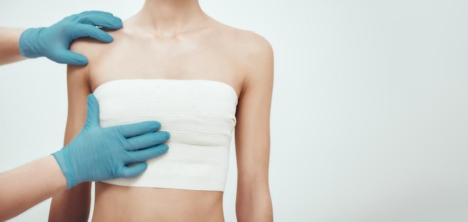 Increase your breast size. Cropped photo of woman waiting for plastic surgery while surgeons in blue medical gloves measuring her breast. Plastic surgery concept. Healthcare. Beauty concept.