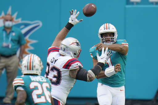 Miami Dolphins quarterback Tua Tagovailoa (1) throws a pass to running back Salvon Ahmed (26) during the first half of an NFL football game against the New England Patriots, Sunday, Dec. 20, 2020, in Miami Gardens, Fla. (AP Photo/Chris O'Meara)