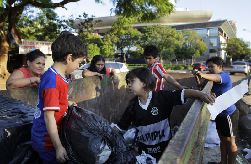 "In this June 26, 2012 photo, members of two families, from left, Perla Soria, Romel Matechip, Maria Belen Britez, Victoria Nunez, Roger Britez, and Sara Aquino search in a trash container for things to recycle, as well as food, along the ""15 de Agosto"" street next to the Legislative Palace, behind, in Asuncion, Paraguay. Across the street from the gleaming Legislative Palace lies a trash-strewn tent camp of Paraguay's landless poor, where pigs root in the dirt and flames lap at the grate of a rudimentary cooking pit. The stark contrast in the capital tells the story of a divided people living under the same red-white-and-blue-striped flag. (AP Photo/Jorge Saenz)"