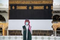 An official from Hajj Ministry wearing a face mask stands in front of the Holy Kaaba in the Grand Mosque during the annual Haj pilgrimage, in the holy city of Mecca