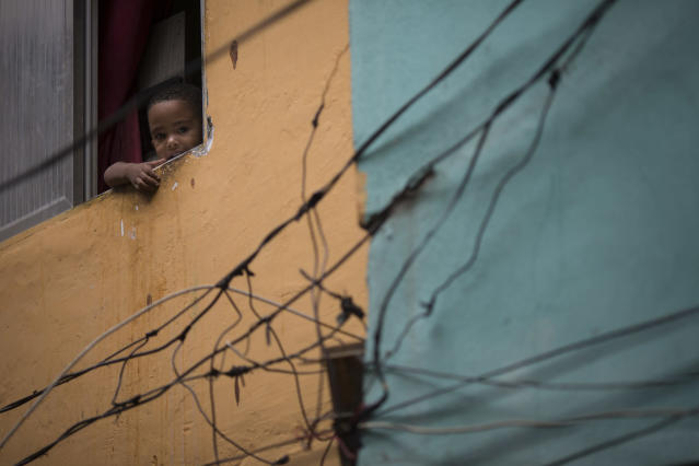 """A young resident looks out from his window as military police officers patrol during an operation in the Mare slum complex, ahead of its """"pacification,"""" in Rio de Janeiro, Brazil, Tuesday, March 25, 2014. Elite federal police and army troops will be sent to the city to help quell a wave of violence in so-called """"pacified"""" slums. Recent attacks on police bases in the favelas is raising concerns about an ambitious security program that began in 2008, in part to secure the city ahead of this year's World Cup and the 2016 Olympics. (AP Photo/Felipe Dana)"""