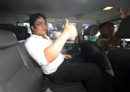 """Ramon """"Bong"""" Revilla, a Philippine action movie hero-turned senator, gives a thumbs-up sign inside a police van after his voluntary surrender at the Sandiganbayan anti-graft court in Manila"""