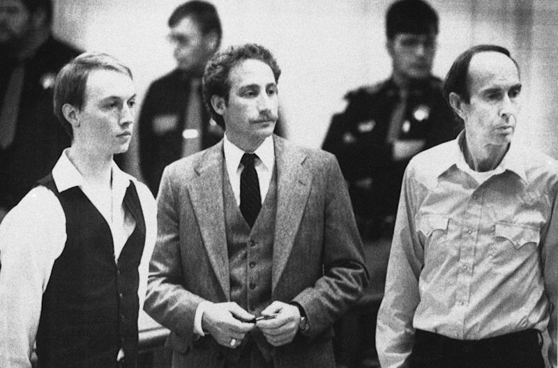 FILE - This Dec. 18, 1984 file photo shows Don Nichols, right, standing with his son, Dan Nichols, left, as they pled not guilty in court in Virginia City, Mont. Standing with them is attorney, Steve Ungar. The U.S. attorney's office in Montana has filed federal drug and weapons charges against Dan Nichols, part of the father and-son duo convicted in kidnapping a world class athlete in 1984, killing a would-be rescuer and eluding authorities for months, April 19, 2012. (AP Photo/File)