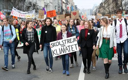 """16-year-old Swedish environmental activist Greta Thunberg and Anuna De Wever, a Belgian climate student activist take part in a protest claiming for urgent measures to combat climate, in central Brussels, Belgium February 21, 2019. The placard reads: """"School strike for climate"""" REUTERS/Yves Herman"""