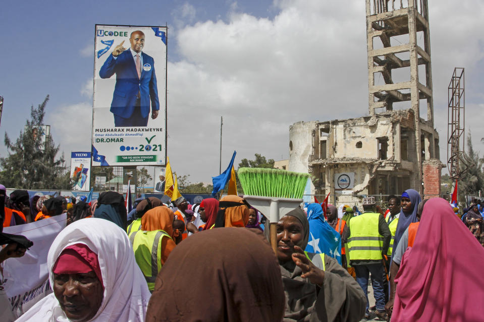 Somalis walk past a billboard showing candidate Omar Abdulkadir Ahmedfiqi in Mogadishu, Somalia Friday, Jan. 29, 2021. As Somalia marks three decades since a dictator fell and chaos engulfed the country, the government is set to hold a troubled national election but two regional states are refusing to take part in the vote to elect Somalia's president and time is running out before the Feb. 8 date on which mandates expire. (AP Photo/Farah Abdi Warsameh)
