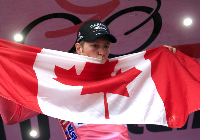Canadian Garmin team cyclist Ryder Hesjedal kisses a Canadian flag as he celebrates after winning the Tour of Italy (Giro d'Italia) cycling race on May 27, 2012 in Milano. AFP PHOTO / LUK BENIESLUK BENIES/AFP/GettyImages