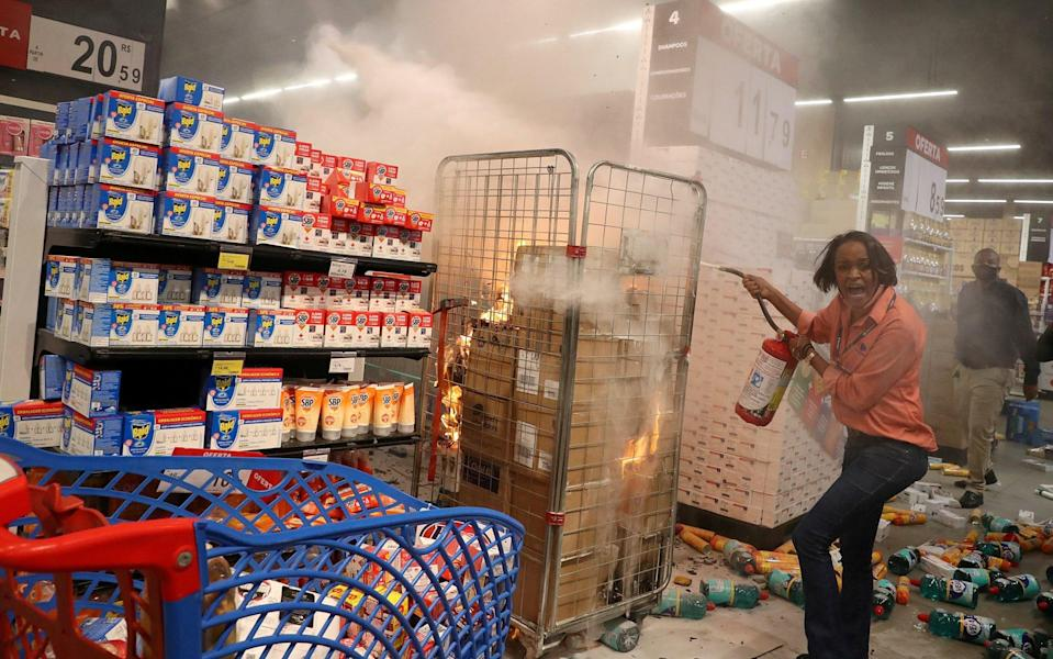 A woman attempts to put out a fire at a vandalised Carrefour store during a march in Sao Paulo - REUTERS/Amanda Perobelli
