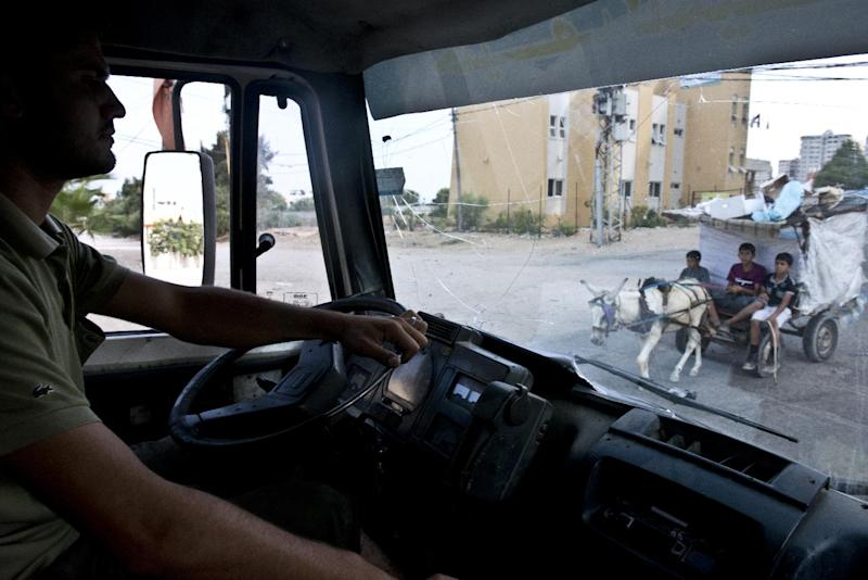 Mahmud drives his water delivery truck on a supply run in Gaza City on August 23, 2014 (AFP Photo/Roberto Schmidt)