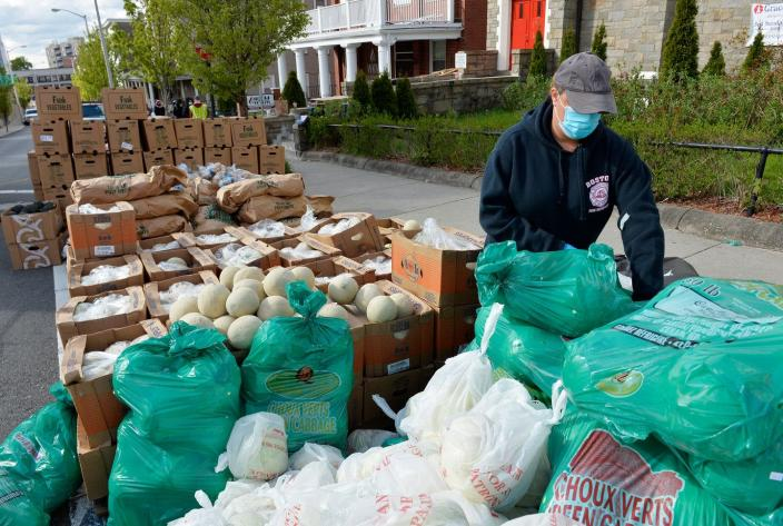 """<span class=""""caption"""">Volunteers load plastic bags for a weekly food pantry service in Everett, Mass., May 10, 2020. Everett has some of the highest COVID-19 infections rates in the state.</span> <span class=""""attribution""""><a class=""""link rapid-noclick-resp"""" href=""""https://www.gettyimages.com/detail/news-photo/volunteers-load-plastic-bags-with-food-and-goods-to-serve-news-photo/1212458851?adppopup=true"""" rel=""""nofollow noopener"""" target=""""_blank"""" data-ylk=""""slk:Joseph Prezioso /AFP via Getty Images"""">Joseph Prezioso /AFP via Getty Images</a></span>"""