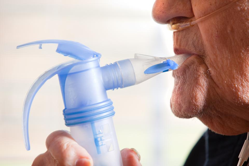 A close up of a 91 year old man using a nebulizer.