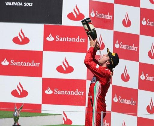 Ferrari's Spanish driver Fernando Alonso celebrates on the podium