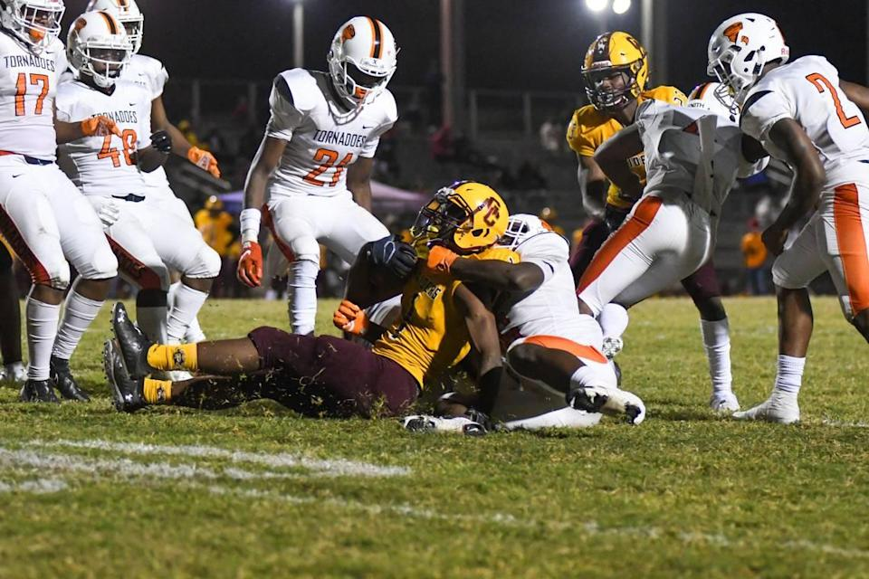 The Booker T. Washington defense brings down Glades Central running back Desmond Washington in the first half against Glades Central in a South Florida Tri-County tournament game on Friday, Dec. 4, 2020, in Belle Glade, Florida.