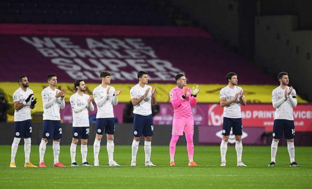 PHOTO: Manchester City players participate in a 'Clap for Captain Tom Moore', who died Feb 2, ahead of the English Premier League soccer match between Burnley and Manchester City at Turf Moor stadium in Burnley, England, Feb. 3, 2021. (Gareth Copley/Pool via AP)
