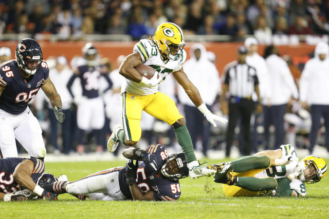 Aaron Jones #33 of the Green Bay Packers leaps over Roquan Smith #58 of the Chicago Bears during the game at Soldier Field on September 05, 2019 in Chicago, Illinois. (Photo by Nuccio DiNuzzo/Getty Images)