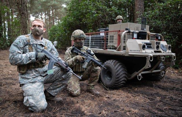 Members of the Army next to a utility delivery vehicle during a live exercise demonstration at Bovington Camp in Dorset