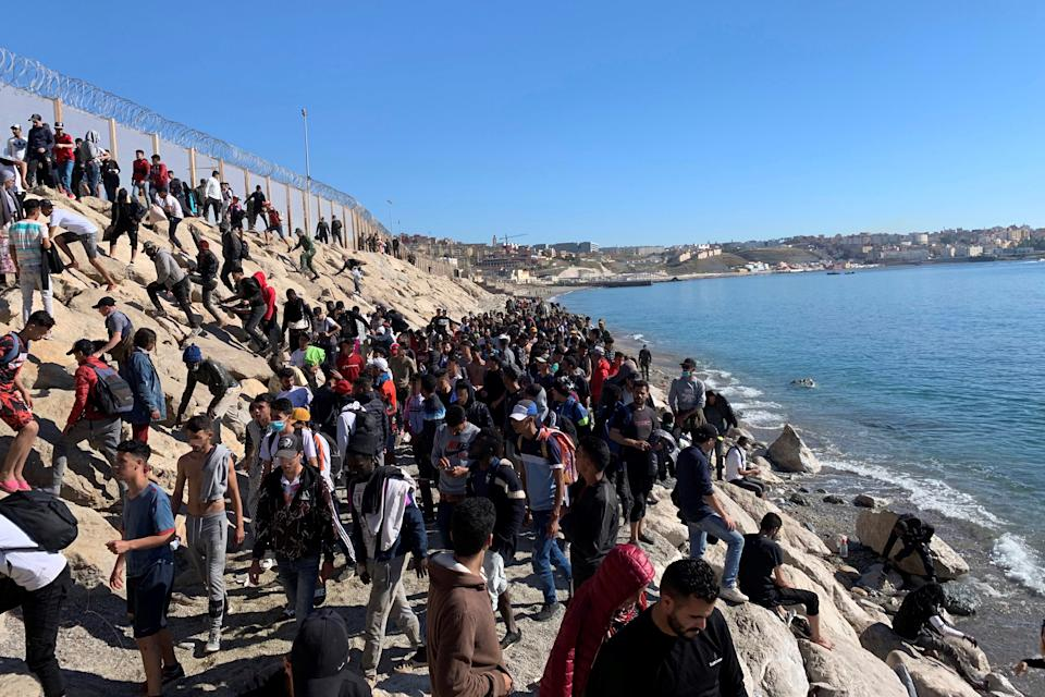 Dozens of people try to cross the border fence separating Fnideq in Morocco and the Spanish city of Ceuta, located in northern Africa. Source: EPA/Mohamed Siali