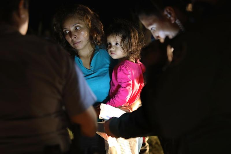 A Honduran mother holds her two-year-old as U.S. Border Patrol as agents review their papers near the U.S.-Mexico border on June 12, 2018 in McAllen, Texas.