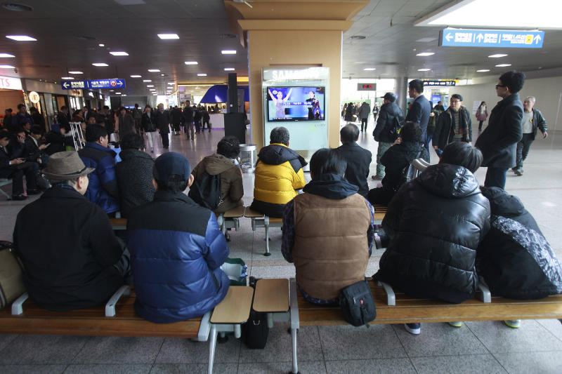 """People watch a TV news report with images of Russia's Adelina Sotnikova, left, and South Korea's Yuna Kim about the result of the women's free skate figure skating final during the 2014 Winter Olympics, at the Seoul Railway Station in Seoul, South Korea, Friday, Feb. 21, 2014. South Koreans still love Kim. The judges, however, are another matter. Yuna Kim, known as the """"Queen"""" in South Korea, finished with the figure skating silver medal at the Sochi Olympics behind Adelina Sotnikova of Russia. That left many South Koreans furious over what they saw as questionable judging. (AP Photo/Ahn Young-joon)"""