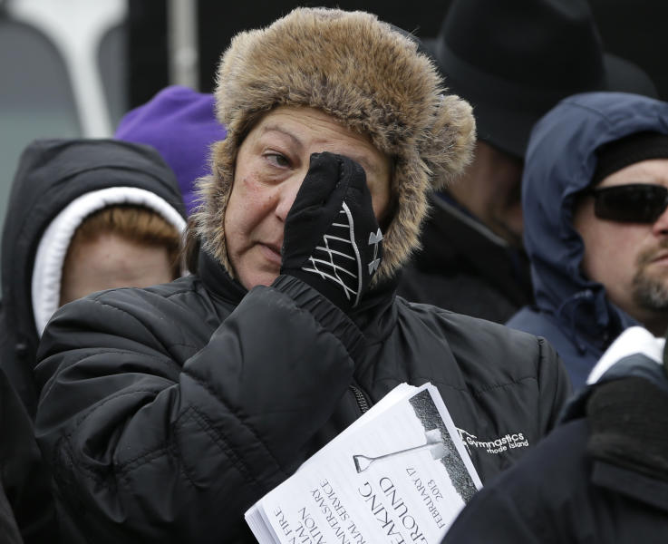 A unidentified woman wipes her face as she reacts during ceremonies held to unveil plans for a permanent memorial on the site of The Station nightclub fire, Sunday, Feb. 17, 2013, in West Warwick, R.I. The 2003 blaze, which broke out when pyrotechnics for the rock band Great White ignited flammable packing foam that had been installed inside the club as soundproofing, took the lives of 100 people. (AP Photo/Steven Senne)