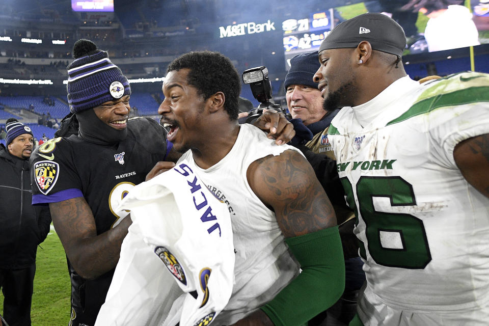 Baltimore Ravens quarterback Lamar Jackson, left, laughs with New York Jets outside linebacker James Burgess, center, as running back Le'Veon Bell, right, looks on. (AP Photo/Nick Wass)