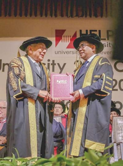 Datuk Mohamed Khaled Nordin (right) receives his certificate from Datuk Paul Leong Khee Seong during the graduation ceremony of HELP University on Saturday. ― Malay Mail pic