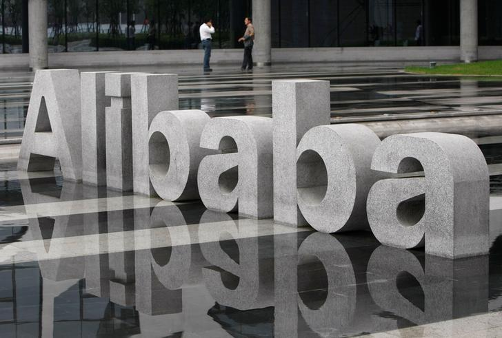 FILE PHOTO: Two men chat beside a logo of Alibaba (China) Technology Co. Ltd at its headquarters on the outskirts of Hangzhou