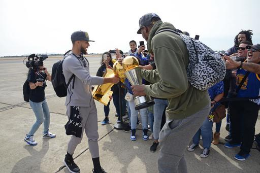 OAKLAND, CA - JUNE 11: Stephen Curry #30 and Kevin Durant #35 of the Golden State Warriors exit the plane with the Larry O'Brien Championship Trophy and the Bill Russell Finals MVP Trohpy as they arrive at Oakland International Airport on June 11, 2018 in Oakland, California. (Photo by Noah Graham/NBAE via Getty Images)