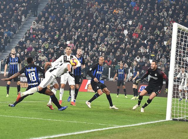 Juventu's Mario Mandzukic, left, scores his side's opening goal during the Serie A soccer match between Juventus and Inter Milan at the Turin Allianz stadium, Italy, Friday, Dec. 7, 2018. (Andrea Di Marco/ANSA via AP)