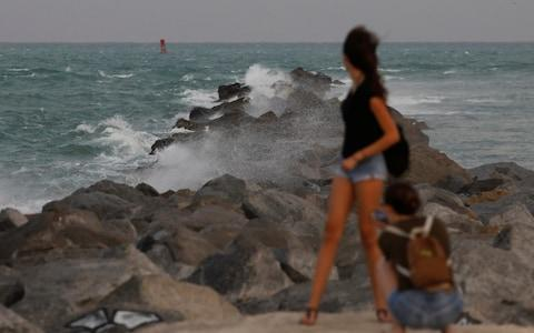 A tourist poses for a picture at a pier in South Beach prior to the arrival of Hurricane Irma to south Florida, in Miami, Florida - Credit: Reuters