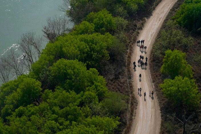 Migrants cross the U.S.-Mexican border into Mission, Texas, on March 23.