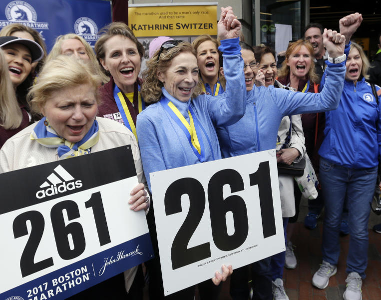 Kathrine Switzer, middle with fist up, the first official woman entrant in the Boston Marathon 50 years ago, cheers at a news conference, Tuesday, April 18, 2017, in Boston, where her bib No. 261 was retired in her honor by the Boston Athletic Association. Switzer is surrounded by runners with her 261 Fearless foundation, and at far left is, BAA President Joann Flaminio. (AP Photo/Elise Amendola)