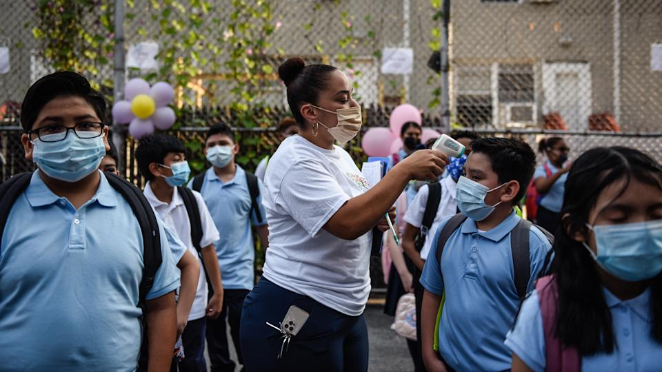 A teacher takes the temperature of students arriving for the first classes at a public school in the Bronx borough in New York, on Monday.