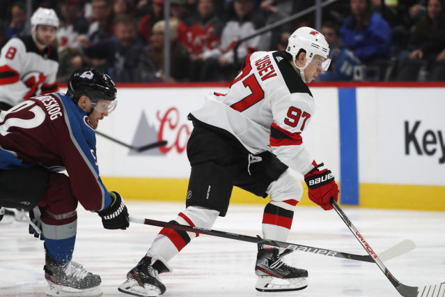 New Jersey Devils left wing Nikita Gusev, right, drives with the puck past Colorado Avalanche left wing Gabriel Landeskog in the second period of an NHL hockey game Friday, Dec. 13, 2019, in Denver. (AP Photo/David Zalubowski)