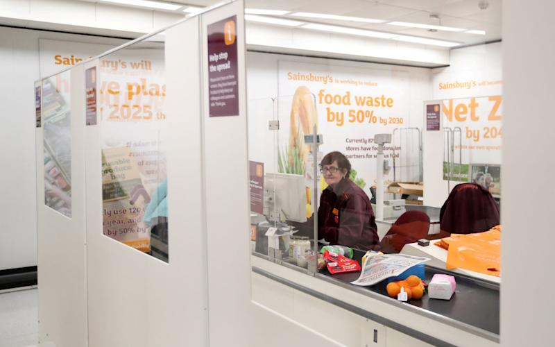 A member of staff at a branch of Sainsbury's supermarket in Harpenden seen behind a screen during the coronavirus outbreak. - Peter Cziborra/Reuters