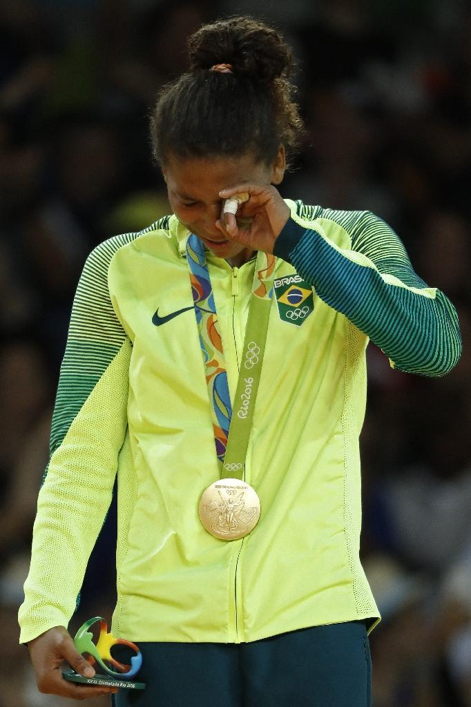 Brazilian judoka Rafaela Silva cries on the podium after winning gold in the women's -57kg judo contest of the Rio 2016 Olympic Games in Rio de Janeiro on August 8, 2016 (AFP Photo/Jack Guez)