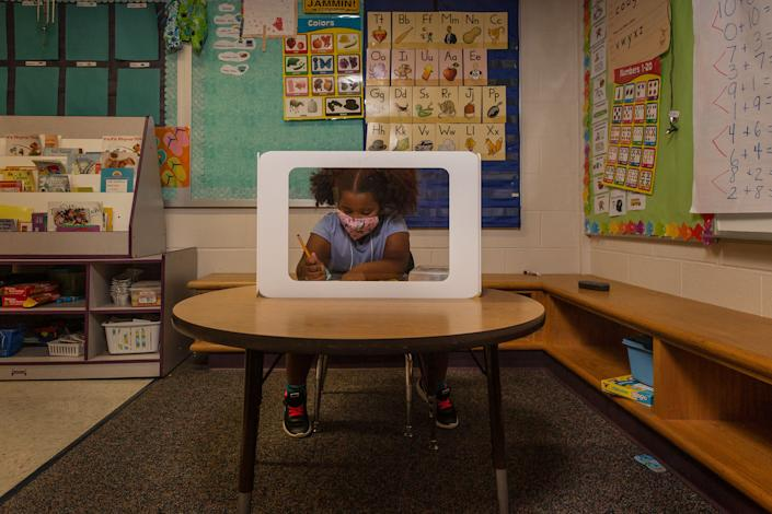 Plastic shields surround the desk where 6-year-old Aven Mullins works | Gillian Laub for TIME
