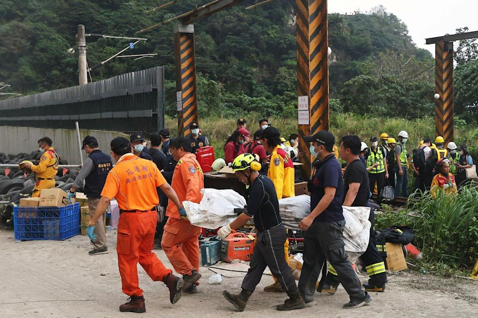 Rescuers carry a body from the site of the deadly crash. Photo: Reuters