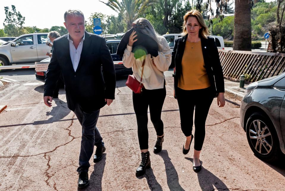 """A British teenager who accused seven Israelis of gang rape covers her face as she comes in the Larnaca District Court on November 01, 2019. - Initially, the Briton had alleged 12 Israelis raped her on July 17 at a hotel in the resort of Ayia Napa, a magnet for younger tourists attracted by its beaches and nightlife. The Israelis aged 15 to 18, several of whom had been detained, were released without charge after she was arrested on suspicion of """"making a false statement about an imaginary crime"""", according to police. (Photo by Iakovos Hatzistavrou / AFP) (Photo by IAKOVOS HATZISTAVROU/AFP via Getty Images)"""